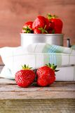 Red fresh strawberries on cloth in front of aluminum cup Stock Image