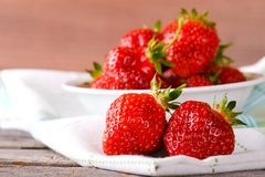 Red fresh strawberries on cloth in front of bowl Stock Photo