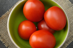 Red fresh tomatoes on green-beige bowl. Royalty Free Stock Photo