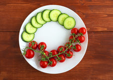 Red fresh  tomatoes on a white plate and sliced cucumber Stock Photography