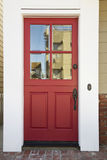 Red front door on an upscale home. Vertical shot of a red front door on an upscale home with reflection in windows, brick flooring and view of doorbell Stock Photography