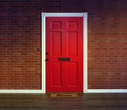 Red front door with welcome mat. Bright red entry door with welcome mat, brick wall and wood porch floor stock photography