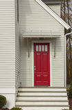 Red front door of white family home Stock Photos