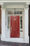 Red Front Door With White Door Frame And Windows On Brick Street Stock Image