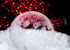 Red frozen bubble. Bubble freezing outside in front of some discarded christmas decoration Stock Photography