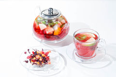 Red fruit and berry tea with raspberries in a glass teapot with mint on isolated white background. Red fruit and berry tea with raspberries in a glass teapot Stock Photo