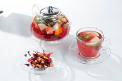 Red fruit and berry tea with raspberries in a glass teapot with mint on isolated white background. Red fruit and berry tea with raspberries in a glass teapot Stock Images