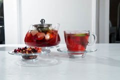 Red fruit and berry tea with raspberries in a glass teapot with mint on isolated white background. Red fruit and berry tea with raspberries in a glass teapot Stock Photography