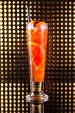Red fruit cocktail with orange in tall glass stock photo