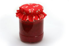 Red fruit jam. Jar of red fruit jam (cornel cherry) with red fabric cover, on white background Stock Photo