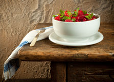 Red fruit on an old table. Antique wooden table with red summerfruit and a vintage napkin Royalty Free Stock Photo