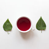 Red fruit tea and green leaves. On white table, above shot Stock Images