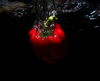 Red fruit in water. Red fruit falling in to the water Royalty Free Stock Photos