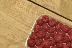 Red-fruited raspberries in plastic box on wooden background. Raspberries background. Close-up.  Royalty Free Stock Photos