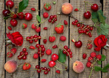 Red fruits and flowers. On wooden background stock images