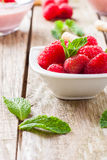Red fruits. Fresh raspberry and strawberry with mint leaves on white bowl Stock Photography