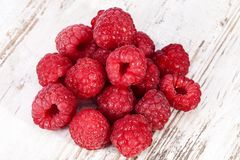 Red fruits of raspberry on wooden plank background, close up. Stock Images