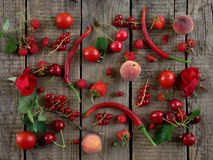 Red fruits, vegetables and flowers. On wooden background royalty free stock images