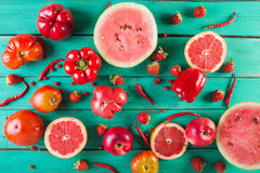 Red fruits and vegetables on a turquoise wooden background. Colorful festive still life. Stock Images