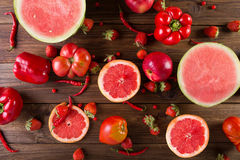 Red fruits and vegetables on a wooden background. royalty free stock photos