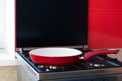 Red frying pan on a gas stove Royalty Free Stock Images