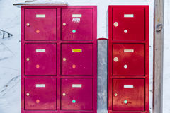 red and fuchsia metallic mailboxes in the snow Royalty Free Stock Image