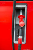 Red fuel nozzle at gas station Royalty Free Stock Photography