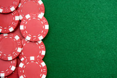 Red gambling chips on green background stock photos