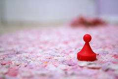 Red game piece. Red game pawn or game piece on a pink rug royalty free stock photo