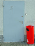 Red garbage can in front of a dirty door Royalty Free Stock Images