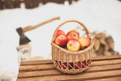 Red garden apples in a wicker picnic basket, on a wooden bench on a winter day, close-up. In the background, fuel wood and an axe royalty free stock image
