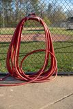 Red Garden Hose hangin on fence at baseball field stock image