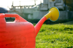 Red Garden watering can on green grass, in the sun Stock Image