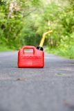 Red Gas Can. A red plastic gas can sitting in the middle of a country road royalty free stock photography