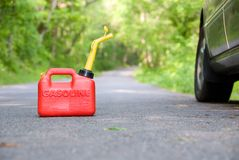 Red Gas Can. A red plastic gas can sitting in the middle of a country road next to a car stock photography
