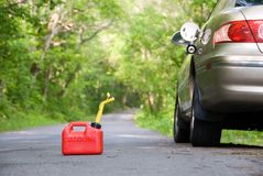Red Gas Can. A red plastic gas can sitting in the middle of a country road next to a stranded car.  Focus is on the gas can Royalty Free Stock Images
