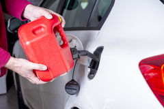 Red gas can adds fuel to an automobile. Adding gas to a car with a can stock photo