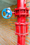 Red gas pipe with blue valve. On brick wall Stock Image