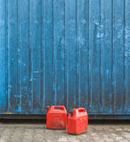 Red gasoline cans. Two red gasoline cans in front of a blue container wall Stock Image