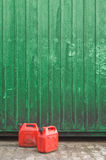 Red gasoline cans. Two red gasoline cans in front of a green container wall Stock Images