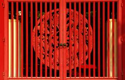 Red gate. Red wooden gate with a carved round symbol in a Buddhist temple in Thailand stock photography