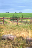 Red gate leads to a meadow and lush field. Stock Images