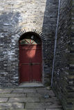 Red door in the old wall corner Royalty Free Stock Photos