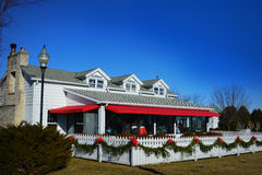 Red Geranium Restaurant. The Red Geranium Restaurant in Lake Geneva, Wisconsin at Christmas time. The white picket fence has Christmas evergreen swags and red royalty free stock images