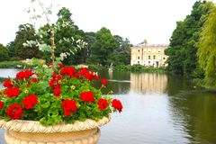 Red Geraniums Overlooking Lake. This idyllic scene encompasses an urn of red geraniums, weeping willow trees and a lake behind an old manor house stock image