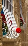 Red geraniums on the window with bars, Malta Royalty Free Stock Photo