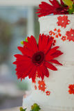 Red Gerber Daisy on Wedding Cake. A bright red gerber daisy decorates a wedding cake with white butter cream frosting stock image