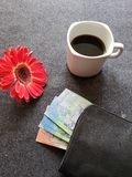 Red gerbera flower, coffee cup and black wallet with australian dollars banknotes on the gray desk. Objects in workspace for business woman royalty free stock photo