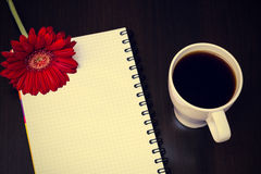 Red gerbera flower, cup of coffee and notebook on the wooden des Royalty Free Stock Image