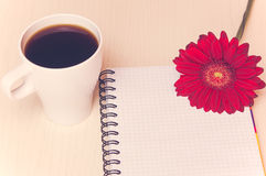 Red gerbera flower,cup of coffee and notebook on the wooden desk Stock Photos